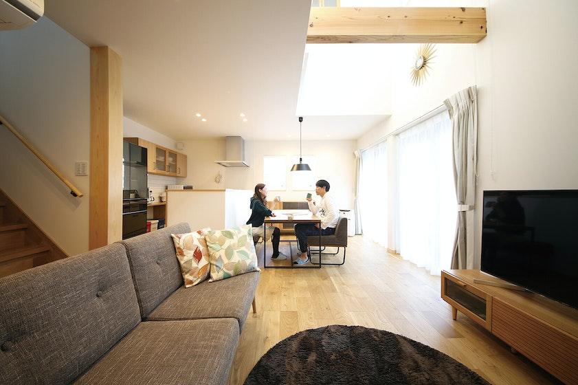 設計士の提案で対面型にしたキッチンと、吹き抜けと大きな窓から光が差し込み明るいダイニング。